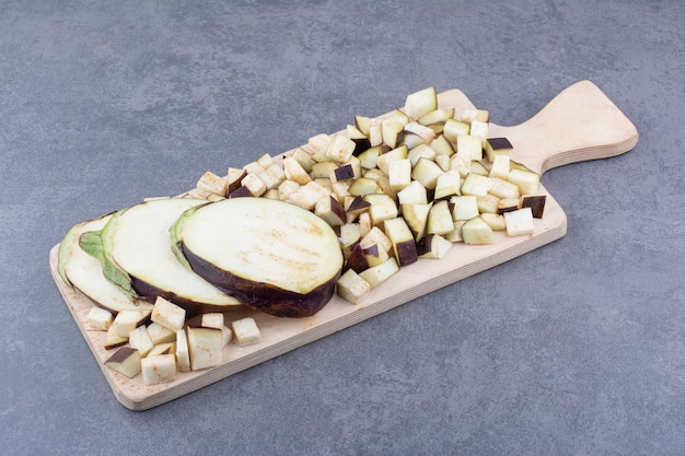 Melanzane affettate e tritate su un piatto di legno
