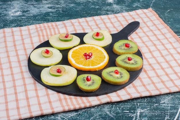 Insalata di frutta affettata e tritata in un piatto sulla superficie blu.
