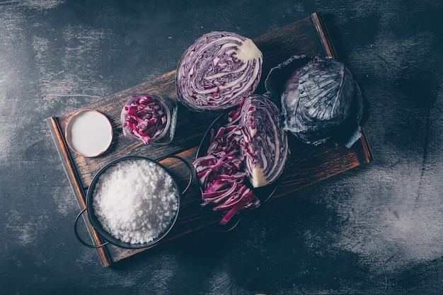 Sliced and chopped red cabbage on a serving tray on a dark textured background. top view.