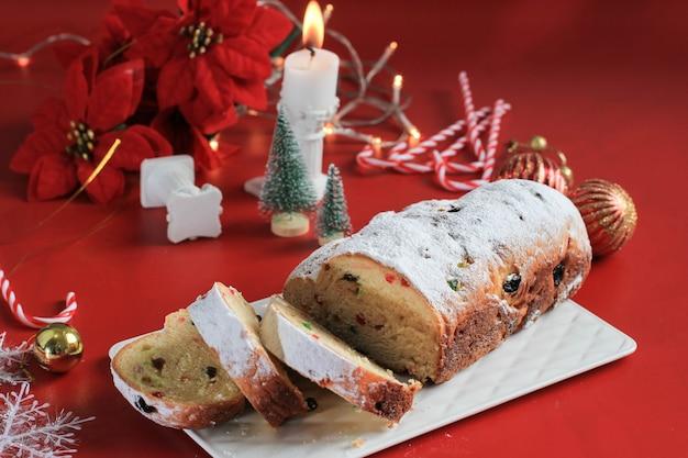 素朴な背景にスライスされたクリスマスシュトーレン。ドイツの伝統的なクリスマスのお祝いペストリーデザート。クリスマスのためにシュトーレン、赤いコンセプト