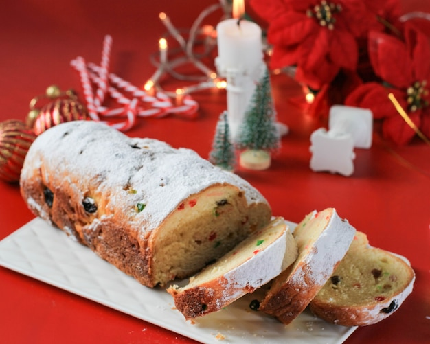 Sliced christmas stollen on rustic background. traditional christmas festive pastry dessert from german. stollen for christmas, red concept