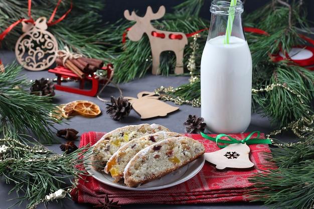 ドライフルーツとミルクのボトルでシュトーレンのクリスマスのおいしいスライス。サンタの御馳走。クリスマス作文。水平フォーマット