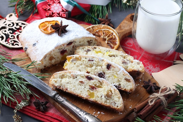Sliced christmas tasty stollen with dry fruits and glass of milk. traditional german treats.