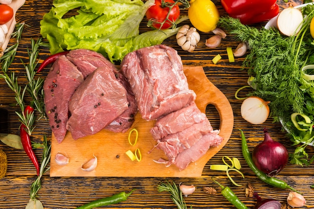 Sliced chunks of red raw meat on cutting board over wood grain table with various fresh greens and herbs surrounding it