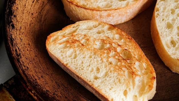 Sliced ciabatta is fried in a pan. slice for bruschetta or breakfast. rosy toast