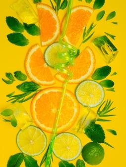 노란색 바탕에 민트와 바 질 잎과 레몬과 오렌지의 슬라이스 서클. 얼음 레모네이드 개념입니다.