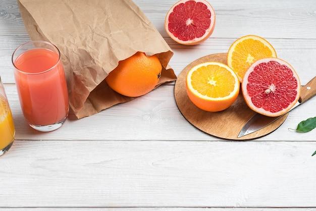 Нарезанные цитрусовые и цитрусовые соки на деревянном столе апельсин и грейпфрут
