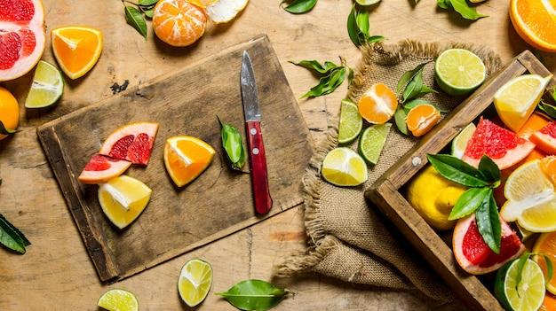 얇게 썬 감귤류 과일-자몽, 오렌지, 귤, 레몬, 라임 상자가있는 이전 보드에.