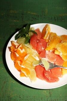Нарезанные цитрусовые на тарелке, на деревянных фоне