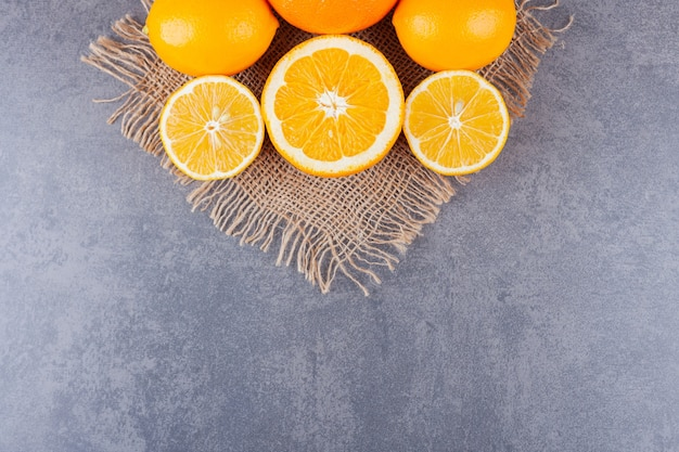 Sliced citrus fruits placed on a stone table.