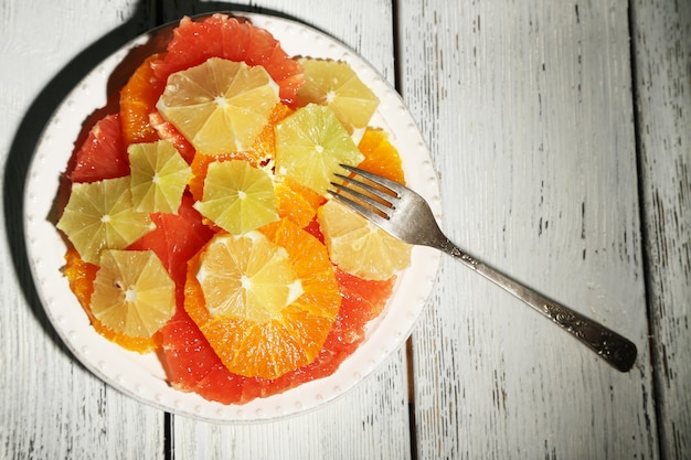 Sliced citrus fruits on plate, on wooden table