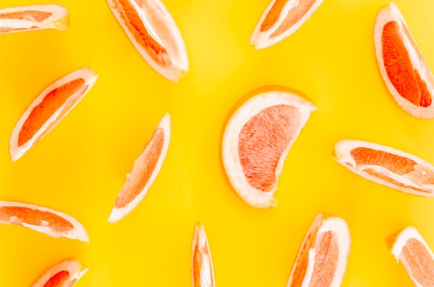Sliced citrus fruits on yellow background
