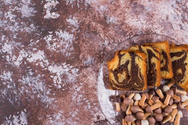 黒い背景にガラスの大皿にクッキーとココアのパイをスライス