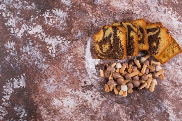 Нарезанный какао-пирог с печеньем в стеклянной тарелке, вид сверху