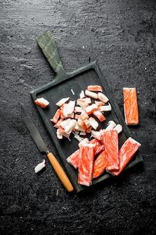 Нарезанные крабовые палочки на разделочной доске. на черном деревенском столе