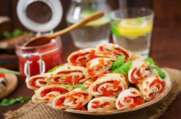 Sliced crepes with cream cheese and red caviar