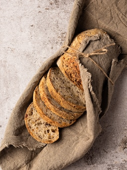 Sliced crusty bread is wrapped in burlap tied with string the background is structural