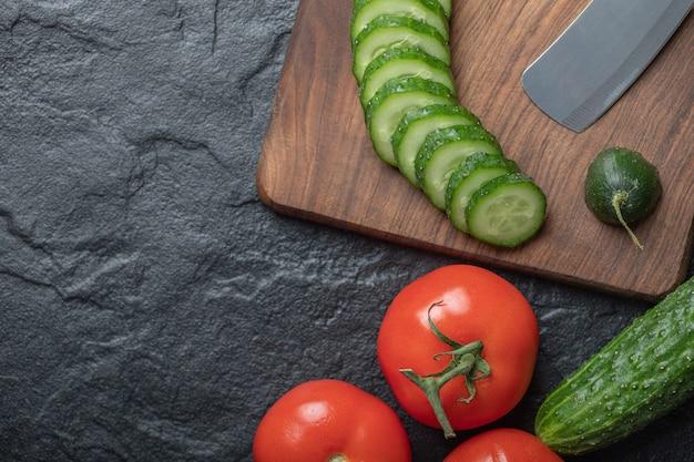 黒の背景にきゅうりとトマトをスライスしました。高品質の写真