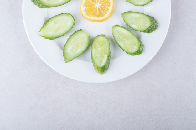 きゅうり、レモン、パセリを皿の上、大理石の上でスライスしました。