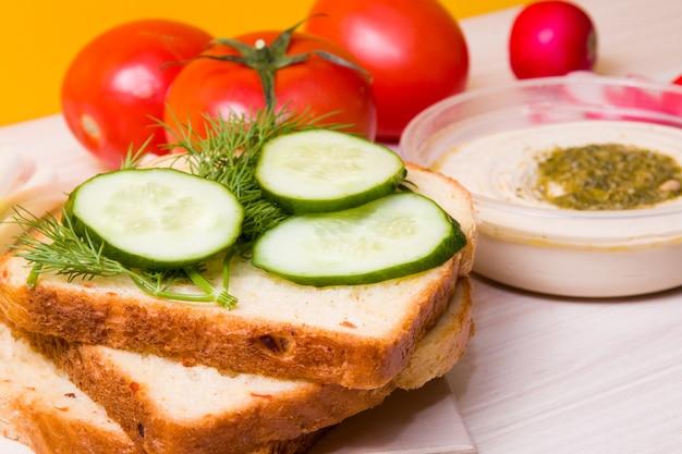 スライスしたパン、野菜、表面にフムスが入ったボウルにスライスしたキュウリ