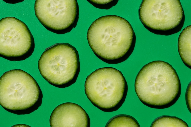 Sliced cucumber pattern on a green background