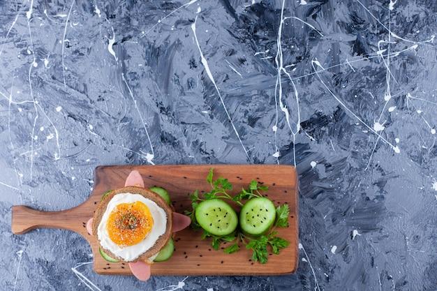 Cetriolo affettato e panino su un tagliere, su sfondo blu.