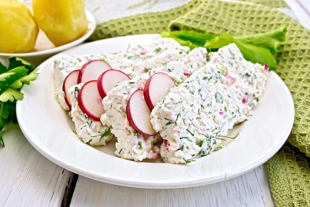 ディルと大根、青玉ねぎ、皿にサラダ、茹でたジャガイモ、ナプキン、軽い木の板にパセリを添えたスライスした豆腐テリーヌ