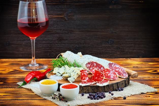 ダークウッドの素朴な背景にスパイスと赤ワインのグラスでスライスした硬化ソーセージ。