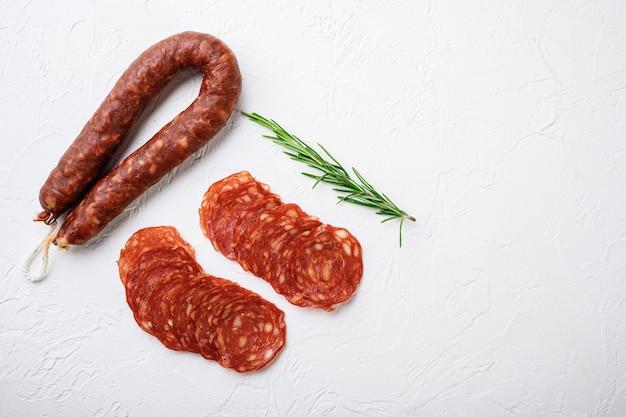 Нарезанные куски колбасы салями чоризо на белой текстурированной поверхности с пространством для текста.