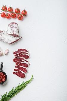 Нарезанные ломтики лонганиза, сухая вяленая испанская колбаса с травами и специями на белой поверхности, вид сверху с копией пространства