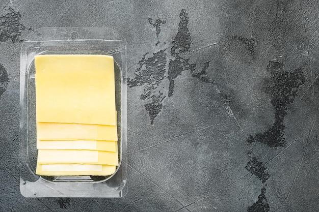 スライスしたおいしいエダムチーズセット、プラスチックパック、灰色の石の背景、上面図フラットレイ、テキスト用のコピースペース