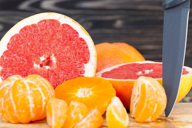 Нарезанный вкусный ароматный кислый грейпфрут и апельсиновые мандарины