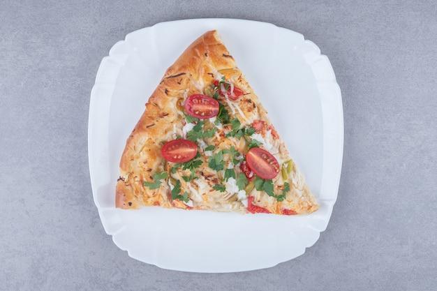 Нарезанная вкусная горячая пицца с помидорами на белой тарелке