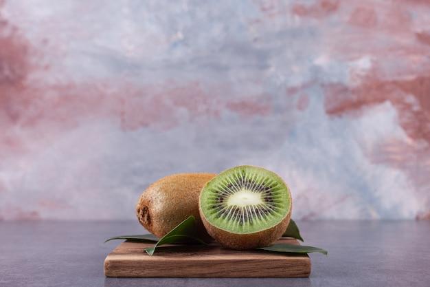 Affettato delizioso kiwi con foglie poste su un piatto di legno.