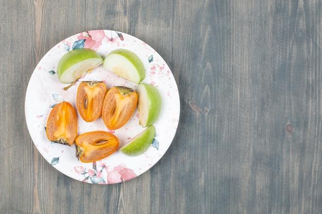 スライスした青リンゴとスライスしたおいしい柿
