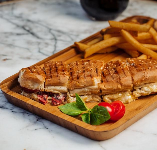 Нарезанный донер с картофелем фри и овощами на деревянной доске