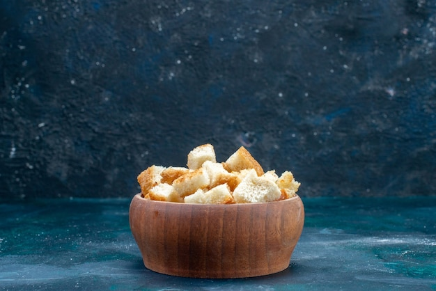 Sliced dried rusks inside brown bowl on dark