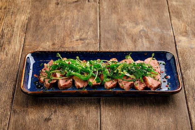 木製の背景に海藻チュカとスライスした乾燥熟成ロースト鴨胸肉