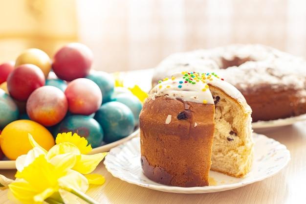 Нарезанный пасхальный православный сладкий хлеб, кулич, крашеные яйца и букет нарциссов. яркий солнечный свет. традиционный пасхальный завтрак. выборочный фокус.