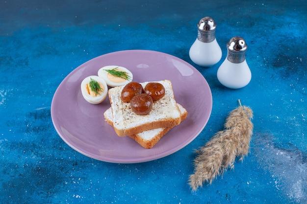 Нарезанное яйцо и варенье на сырном хлебе на тарелке, на синей поверхности.