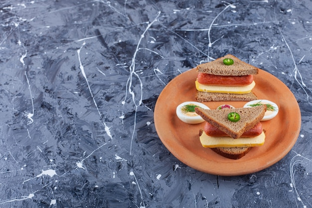 Нарезанное яйцо рядом с колбасой между двумя ломтиками хлеба на тарелке, на синем.