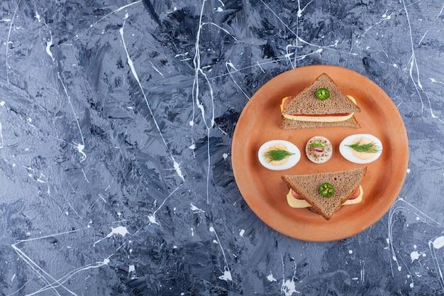 Uovo affettato accanto alla salsiccia tra due fette di pane su un piatto, sul blu.
