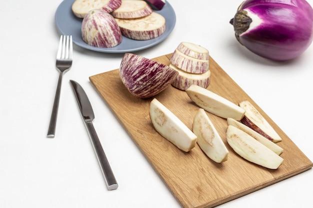 まな板と灰色のプレートにスライスしたナス。テーブルの上のフォークとナイフと丸ごと紫色のナス。上面図。白色の背景。