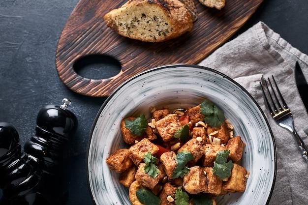 Ломтики нарезанных баклажанов в тарелке на сером фоне. готовим жареные баклажаны. баклажаны нарезанные и обжаренные в кляре.