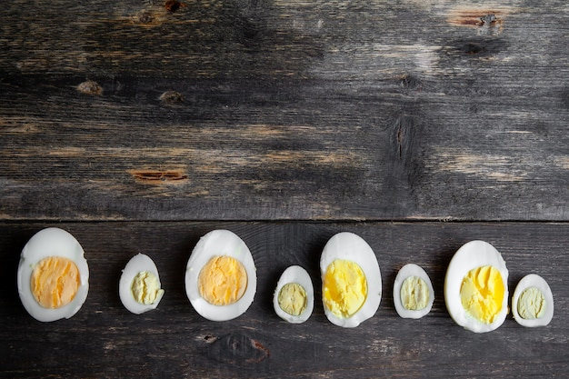 Sliced eggs on old wooden background, top view.