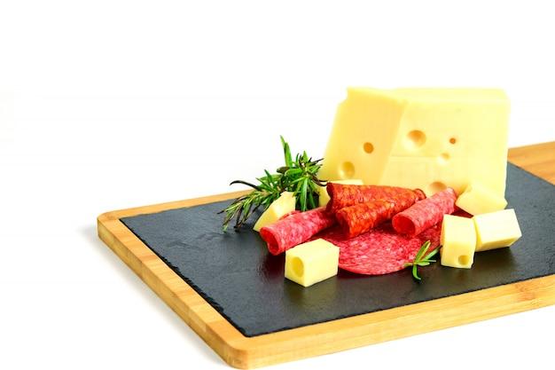 Нарезанный сыр эмменталь, салями и чоризо на доске тапас.