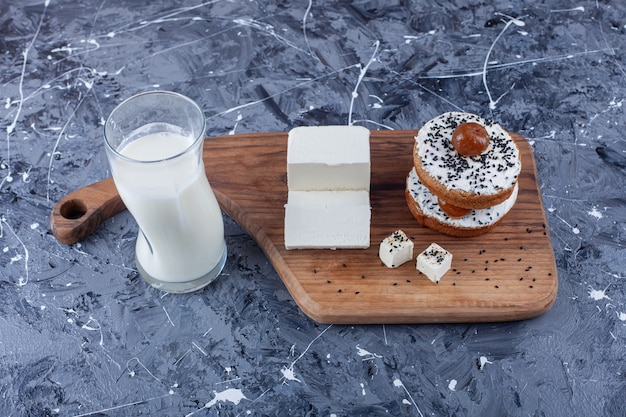 Sliced feta cheese and cheese bread on a cutting board next to a glass of milk, on the blue surface.
