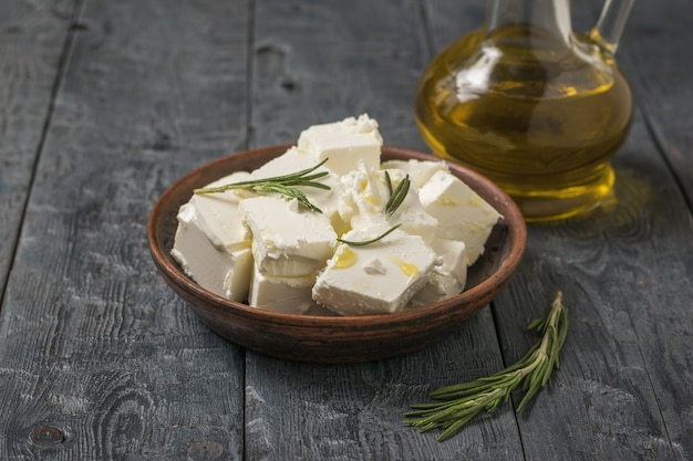 Sliced feta cheese in a clay bowl and olive oil on a wooden table. natural cheese made from sheep's milk.