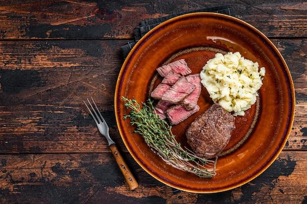 Нарезанное филе миньон или стейк из говяжьей вырезки на деревенской тарелке с картофельным пюре. темный деревянный фон. вид сверху. скопируйте пространство.