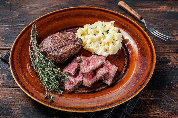 Нарезанное филе миньон или стейк из говяжьей вырезки на деревенской тарелке с картофельным пюре. темный деревянный фон. вид сверху.